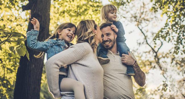 Paar mit zwei Kindern auf den Schultern