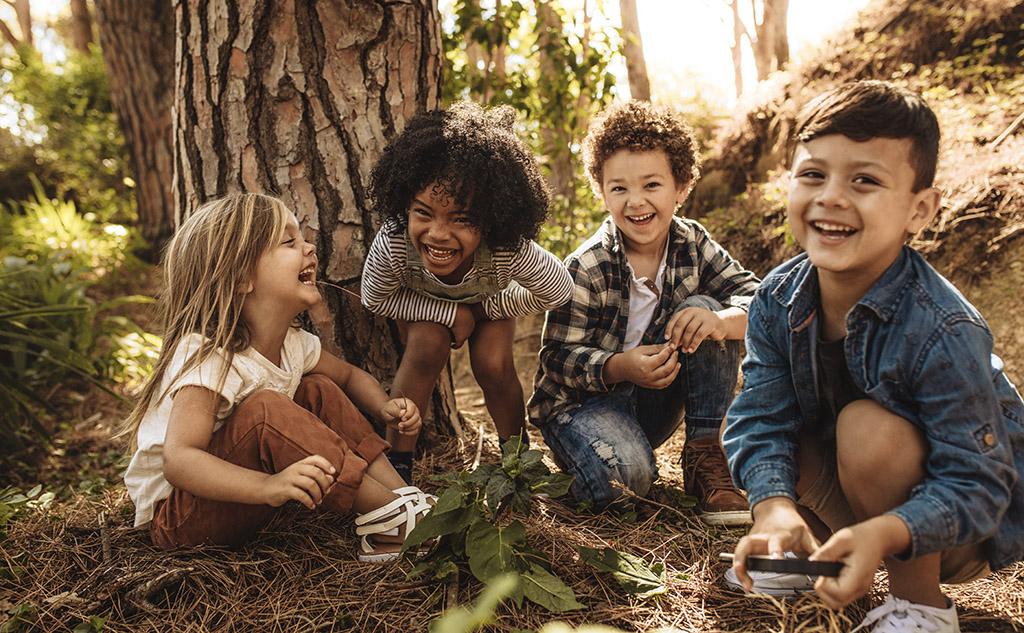 Vier Kinder hocken im Wald und lachen